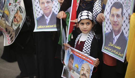 Palestinian supporters of former head of Fatah in Gaza, Mohammed Dahlan, hold posters depicting Dahlan (R) during a protest against Palestinian President Mahmoud Abbas in Gaza City December 18, 2014. Dahlan, who lives in exile in the Gulf, is a powerful political foe of Abbas.  REUTERS/Mohammed Salem (GAZA - Tags: POLITICS CIVIL UNREST) - RTR4IJ93