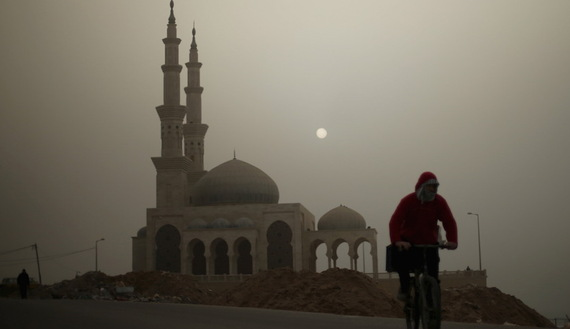 A Palestinian man rides his bicycle in front of a mosque on a stormy day in Gaza January 18, 2016. REUTERS/Mohammed Salem  - RTX22XLX